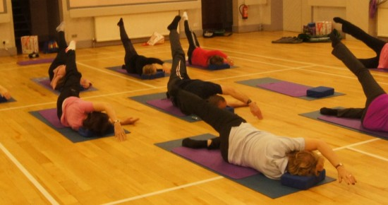 Pilates class conducting mat exercises